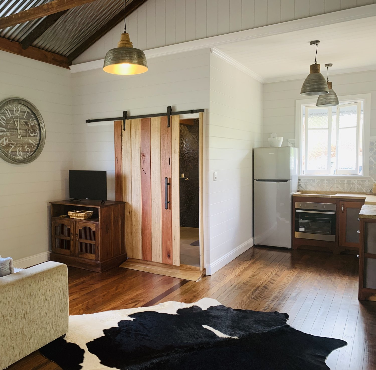 Hand crafted door in native timbers. Kitchen. Wide door. Low bench. Cow skin rug. The Grain Shed Retreat is designed for disability access. Owned and operated by NDIS service provider Darling Downs Wellness Therapies.