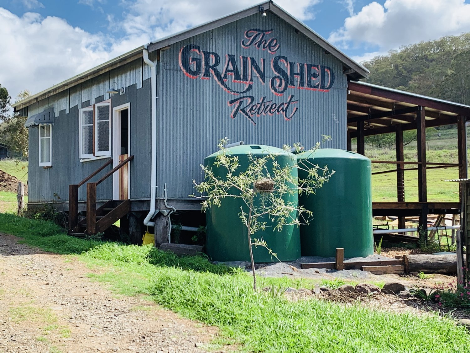 The Grain Shed Retreat outside view. Verandah visible. The Grain Shed Retreat is designed for disability access. Owned and operated by NDIS service provider Darling Downs Wellness Therapies.